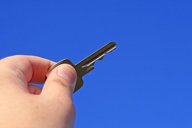 ruka, klíč, modré pozadí