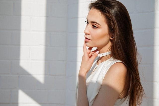 žena u světlé stěny, má dlouhé hnědé rovné vlasy a světlou halenku