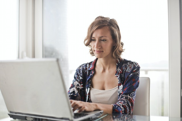 žena v košili sedí za notebookem